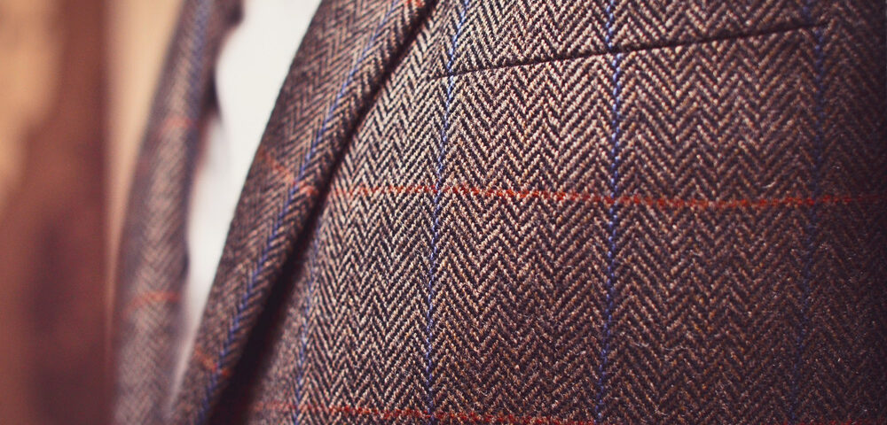 Classic tweed men's jacket with closeup on wool fabric texture.